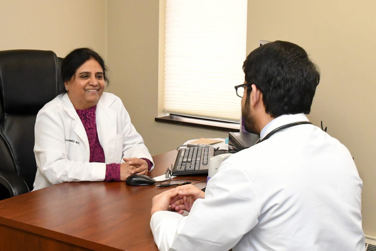 Faculty physician Bader Ahmed MD talks over a patient case with a resident physician at the Hurley Combined Medicine/Pediatrics Resident Clinic.